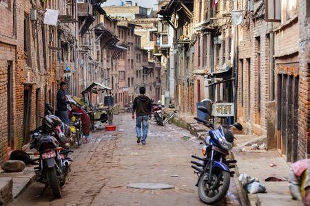 3rd ancient: BHAKTAPUR, NEPAL, NOVEMBER 25, 2010: A man is walking in a narrow ancient street in Bhaktapur, Nepal