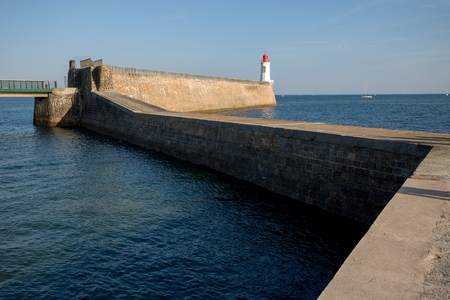 vendee: Zigzag pier and lighthouse in a maritime port