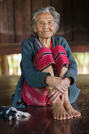 BAM MUANG PAM, THAILAND, NOVEMBER 22 : An elderly Karen tribe woman, Thai ethnicity, is posing in her wooden house, her cat lying beside, in the village of Bam Muang Pam, north Thailand on November 22, 2012