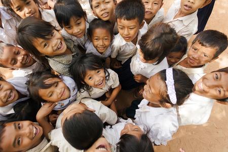 niños pobres: Siem Reap, Camboya, 04 de diciembre de 2012: grupo de niños alegres que presentan en un patio de la escuela en Siem Reap, Camboya