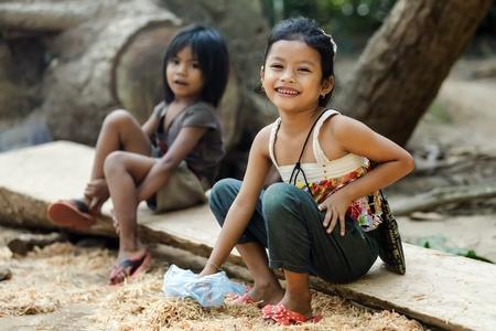 niños pobres: Angkor Wat, Camboya, 06 de diciembre de 2012: Dos niñas camboyanas están sentados cerca del templo para la venta de algunos recuerdos a los turistas en wat Angkor, Siem Riep, Camboya