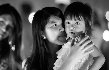 south asian ethnicity: Chiang Mai, NOVEMBER 16, 2013: A young mother is holding her daughter during the Yee Peng lantern buddhist festival in Chiang Mai, Thailand