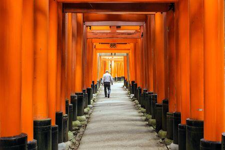 Man walking in the fushimi-inari shrine wooden tunnel in Kyoto, Japan