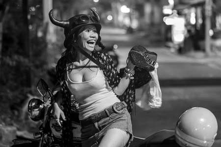 PATTAYA, THAILAND, MARCH 31, 2011: A funny woman wearing an horned helmet is laughing sitting on a motorbike in a Pattaya street, Thailand