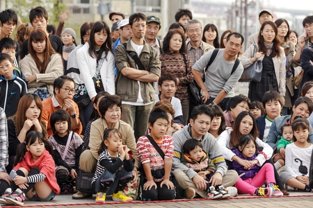 public aquarium: OSAKA, JAPAN, NOVEMBER 13, 2011: Japanese public crowd is watching a magician show performed at the aquarium square in Osaka, Japan Editorial