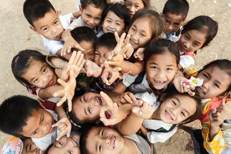 laotian: SAYABOURY, LAOS, FEBRUARY 16, 2012: Group of joyful unidentified kids posing in the schoolyard during the Elefantasia festival on February 16, 2012 in Sayaboury, Laos