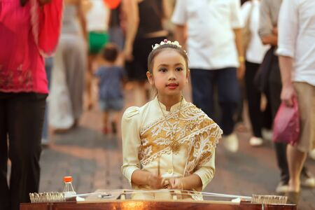playing the market: CHIANG MAI, THAILAND, FEBRUARY 26, 2012: A little girl dressed in traditional clothes is playing dulcimer instrument in the street during the week-end night market in Chiang Mai, Thailand