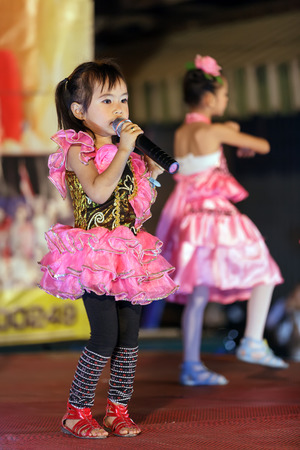 CHIANG MAI, THAILAND, FEBRUARY 26, 2012: Little girls are singing traditional Thai songs on stage during the night week-end market in Chiang Mai, Thailand