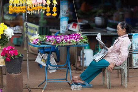 people sitting on chair: THONG PHA PHUM, THAILAND, JULY 07, 2012: A street flower woman seller is sitting and reading a newspaper in the village of Thong Pha Phum in the Kanchanaburi province, Thailand Editorial