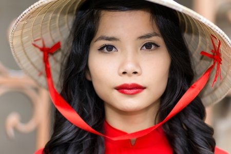 Pretty young Vietnamese woman in a red top with matching lipstick wearing straw hat, close up face portrait looking into the camera photo