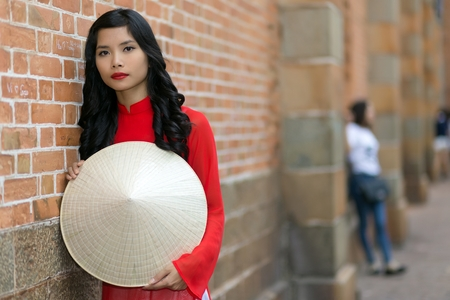 non la: Attractive young Vietnamese woman wearing traditional clothing holding her hat in front of her as she leans against a brick building in an urban street looking at the camera Stock Photo