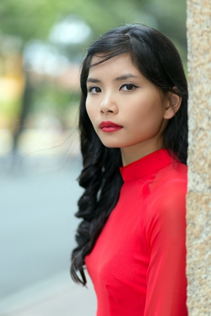 non la: Attractive serious young Vietnamese woman in a vivid red dress leaning on a wall in an urban street turning to look at the camera, close up view of her face Stock Photo