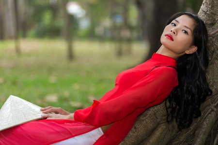 non la: Slender young Vietnamese woman relaxing in a park leaning back against the aerial roots of a tree in her traditional red outfit looking at the camera with a serious expression