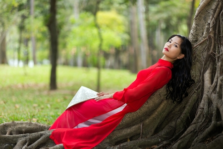 Pretty slim young Vietnamese lady dressed in red traditional clothes relaxing on aerial tree roots in a public park reclining on her back as she stares thoughtfully into the air photo