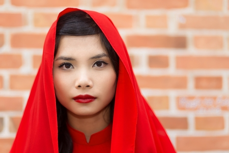 non la: Serene elegant young Vietnamese woman in a traditional red outfit with a scarf over her hair looking directly at the camera with a serious expression against a brick wall with copyspace Stock Photo