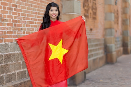 Pretty young Vietnamese woman with a lovely friendly smile holding up a the national flag of Vietnam as she stands in an urban street against a brick wall photo