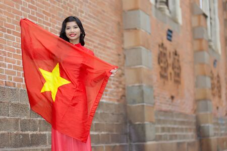 non la: Happy patriotic young Vietnamese woman with a lovely warm smile holding up the national flag in her arms as she stands against brick buildings in an urban street, with copyspace Stock Photo
