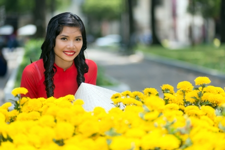 non la: Attractive young Vietnamese woman smiling happily at the camera over a display of yellow flowers in an urban street