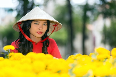 non la: Attractive young Vietnamese woman in a traditional hat looking at the camera with a serious expression over a display of colorful vivid yellow flowers in a park