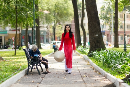 non la: Elegant young Vietnamese woman wearing a traditional red dress walking through a public park past a bench with a person sitting on it Stock Photo