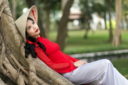 non la: Gorgeous young Vietnamese woman dressed in a traditional red outfit daydreaming as she leans comfortably back against the trunk of tree in an urban park