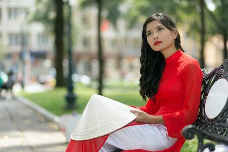 non la: Gorgeous slender young Asian woman in red traditional Vietnamese clothing sitting daydreaming on a park bench in a town