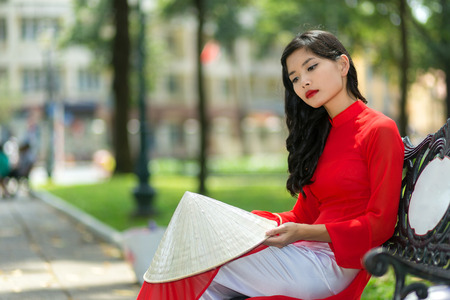 non la: Sad young Vietnamese woman in traditional red clothing sitting on a bench in an urban park with her hat on her knee staring at the ground Stock Photo