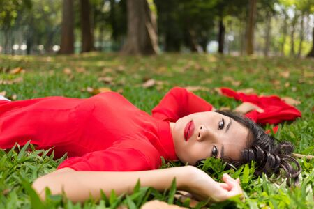 Pretty Vietnamese woman relaxing on the grass lying on her back in a traditional red dress with her arms outstretched looking at the camera photo