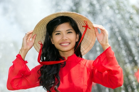 non la: Smiling vivacious Vietnamese woman in a traditional red outfit and conical hat standing in front of a fountain smiling at the camera Stock Photo