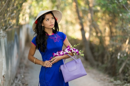 ao: pretty young Vietnamese woman in a stylish blue outfit carrying flowers as she walks through a tree-lined avenue in the park