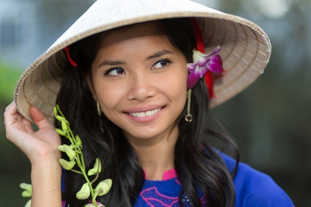 non la: Pretty Vietnamese woman wearing a traditional conical hat with a flower in her hair smiling happily as she looks up into the air Stock Photo