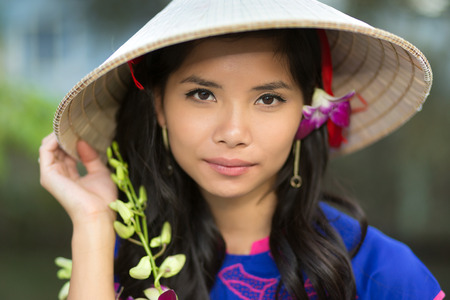 adult vietnam: Attractive serious young Vietnamese woman in a conical straw hat with a fresh flower in her hair looking at the camera with her hand to the brim