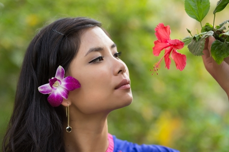 adult vietnam: Pretty Vietnamese girl with a flower in her hair taking a close look at a tropical red hibiscus on the tree, side view with a serious expression against greenery