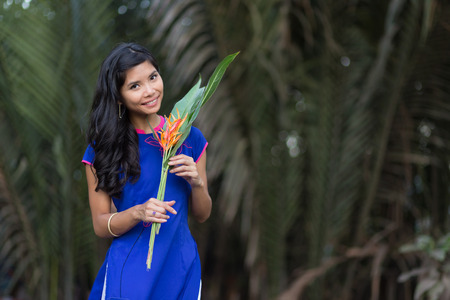 non la: Smiling Young Vietnamese Woman in Blue Dress Holding Fresh Flowers with Big Green Leaves While Looking at the Camera. Stock Photo
