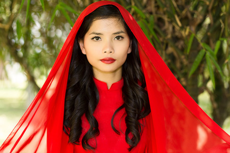 non la: Close up Young Pretty Asian Woman in Red Dress with Head Scarf with Long Wavy hair Looking at the Camera.
