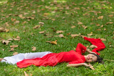 ao: Happy Young Pretty Asian Woman in Red and White Dress Lying Down on Grassland While Looking at the Camera.