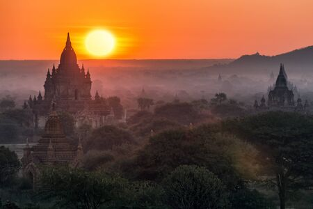 enchanting: Enchanting sunrise in a misty morning over the Bagan religious site in Myanmar Stock Photo