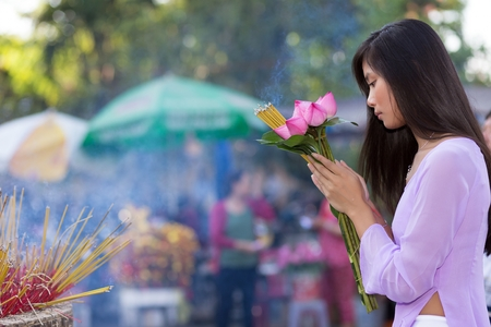 Pretty Vietnamese girl praying as she makes an offering of fresh flowers at a Buddhist shrine during an open air ceremony photo