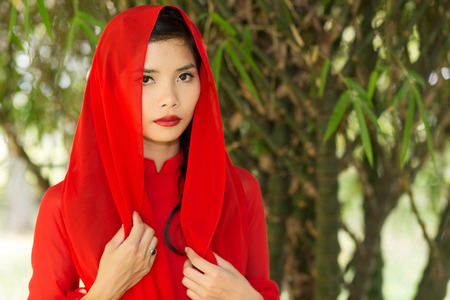 ao: Pretty Vietnamese woman in a red head scarf standing with her hands to her chest looking at the camera with a serious expression Stock Photo