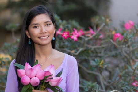 Pretty Asian woman holding lotus flowers bunch Stock Photo