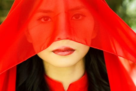 mouth cloth: Close up of serious young Asian woman with red scarf covering her face
