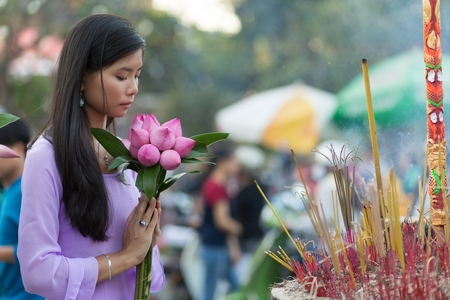 Peace and beauty in prayer as a young Vietnamese woman makes an offering of pretty fresh pink flowers at a Buddhist shrine with burning incense photo
