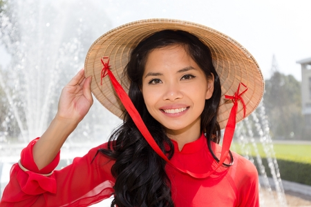 Vietnamese woman in a red Ao Dai and conical hat standing in front of a fountain smiling at the camera