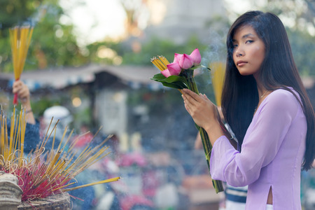 ao: Vietnamese woman praying at temple, holding incense sticks and lotus flowers