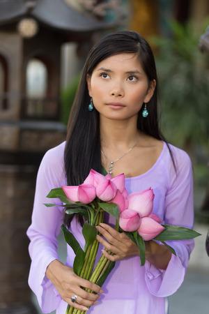 ao: Vietnamese woman holding lotus bud bunch