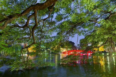 The Hoan kiem lake with the Huc bridge illuminated behind the flamboyant trees, Hanoi, Vietnam