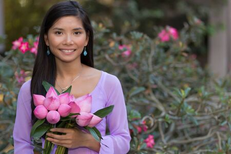 rose tree: Asian woman with lotus flowers bud posing in front of a desert rose tree Stock Photo