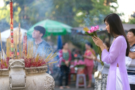 vietnamese: Vietnamese girl praying in Buddhist temple, holding lotus flowers, Saigon, Vietnam
