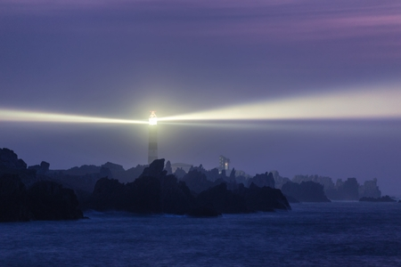 Krachtige vuurtoren 's avonds verlicht, Ouessant eiland, Frankrijk