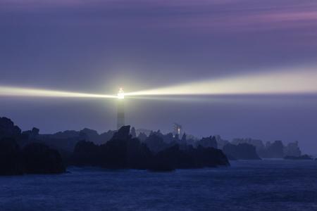 Powerful lighthouse illuminated at night,Ushant island, France